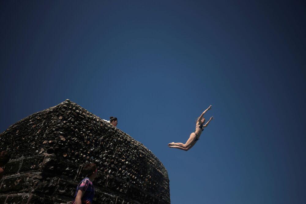 فتاة تقفز إلى مياه البحر حيث يستمتع الناس بالطقس الحار على شاطئ برايتون في برايتون، بريطانيا، 1 يونيو 2021