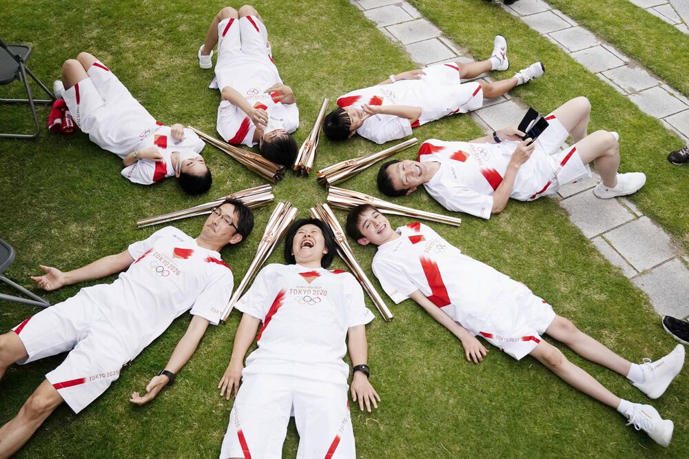 المشاركون في سلسلة تتابع شعلة أولمبياد طوكيو يستلقون في دائرة خلال استراحة في توياما باليابان في 3 يونيو 2021