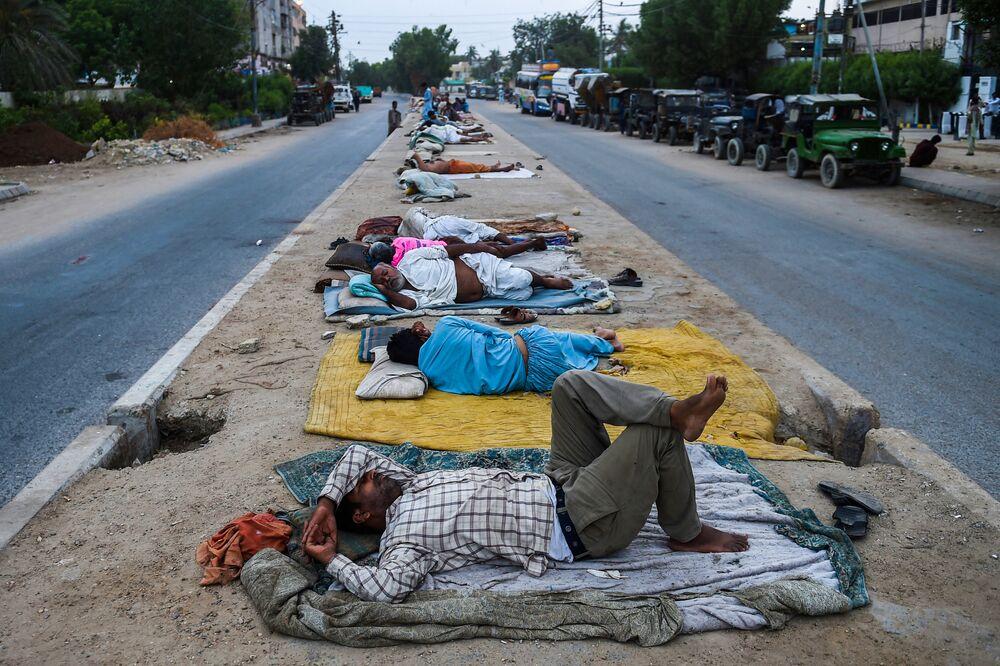 عمال ينامون على حاجز طريق وسط شارع في مدينة كراتشي الساحلية، باكستان في 1 يونيو 2021