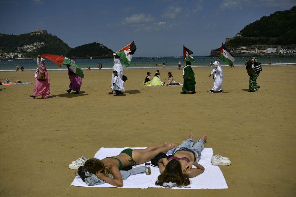 متظاهرون من الصحراء يلوحون بأعلام في مسيرة على الشاطئ في سان سيباستيان، إسبانيا 30 مايو 2021