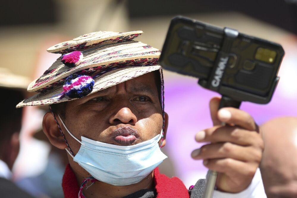 رجل من سكان ميساك من السكان الأصليين يتخذ وضعية أثناء التقاط صورة سيلفي، أثناء احتجاجات مناهضة للحكومة، أثارته الاقتراحات في رفع الضرائب على الخدمات العامة والوقود والأجور والمعاشات التقاعدية في بوغوتا، كولومبيا 2 يونيو 2021