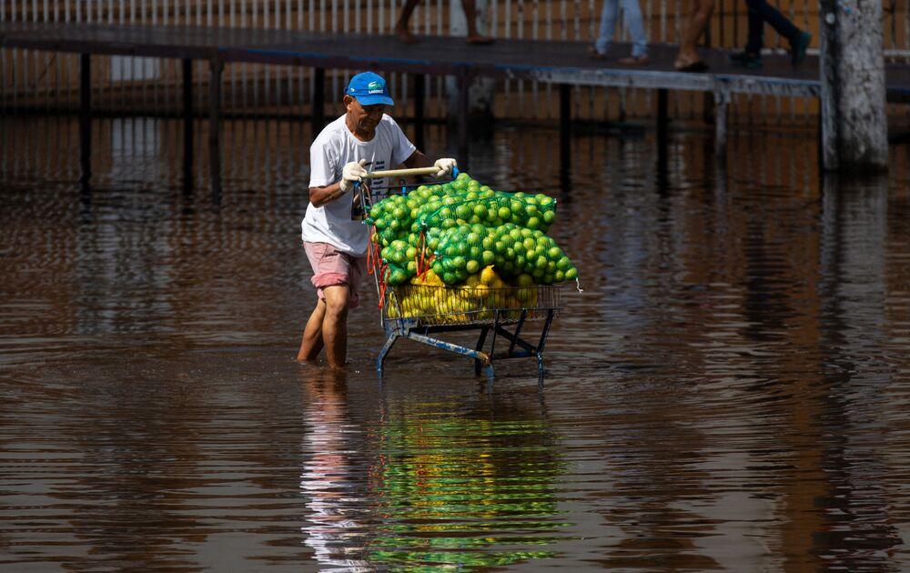 رجل يدفع بعربة الفاكهة وهو يسير على طول شارع غمرته المياه في وسط مدينة ماناوس، عاصمة ولاية أمازوناس البرازيلية، في 1 يونيو 2021، وهو يوم مياه ريو نيغرو، أحد روافد نهر الأمازون، بلغ ارتفاعه 29،98 مترًا، مسجلاً مستوى قياسيًا جديدًا لموسم الفيضانات.