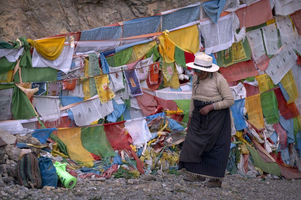 امرأة تبتية تسير أمام أعلام الصلاة في ضريح بوذي في نامتسو، في منطقة التبت ذاتية الحكم بغرب الصين، خلال زيارة نظمتها الحكومة للصحفيين الأجانب، 2 يونيو 2021