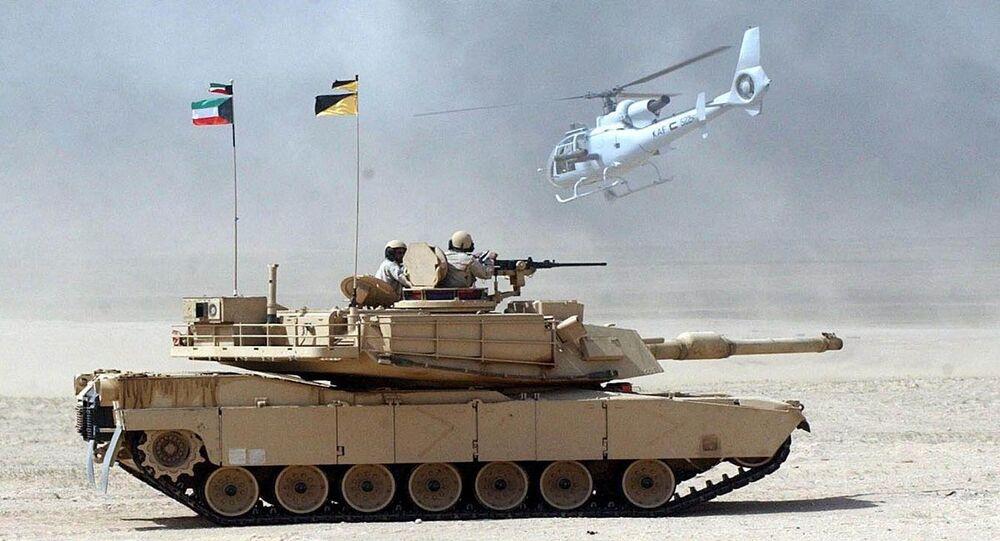 مروحية عسكرية تحلق فوق إحدى الدبابات التابعة للجيش الكويتي خلال مناورة عسكرية
