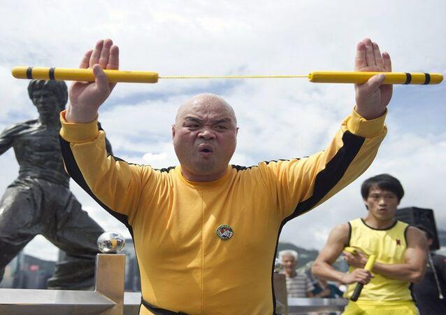 لاعب كونغ فو يمارس بعض الحركات القتالية أمام تمثال لمدرب الفنون القتالية الصين الراحل بروس لي