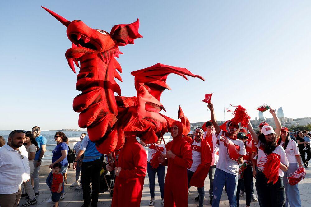مشجعون يحملون أعلام ورموز فرق منتخبات سويسرا وويلز وتركيا أثناء استعراضهم في وسط باكو في أذربيجان، 13 يونيو 2021