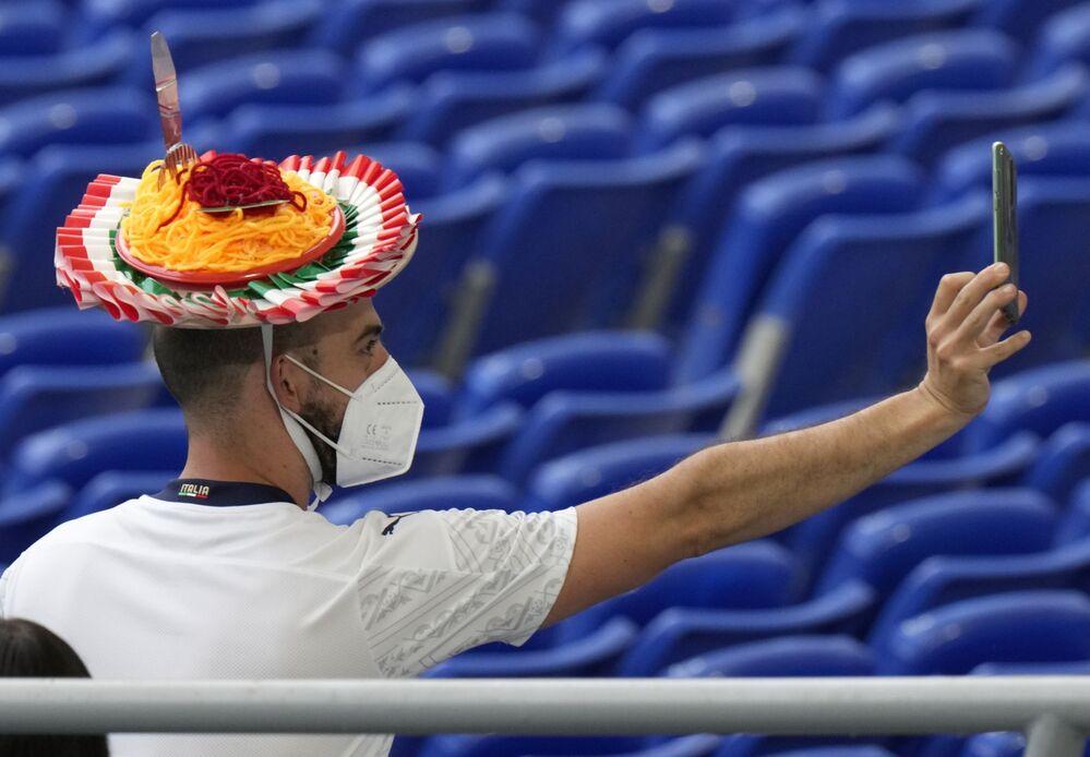 مشجع إيطالي يرتدي قبعة ملونة، يلتقط صورة سيلفي قبل مباراة المجموعة A في بطولة يورو 2020 بين منتخبي تركيا وإيطاليا، في ملعب روما الأولمبي أولمبكو، إيطاليا 11 يونيو 2021