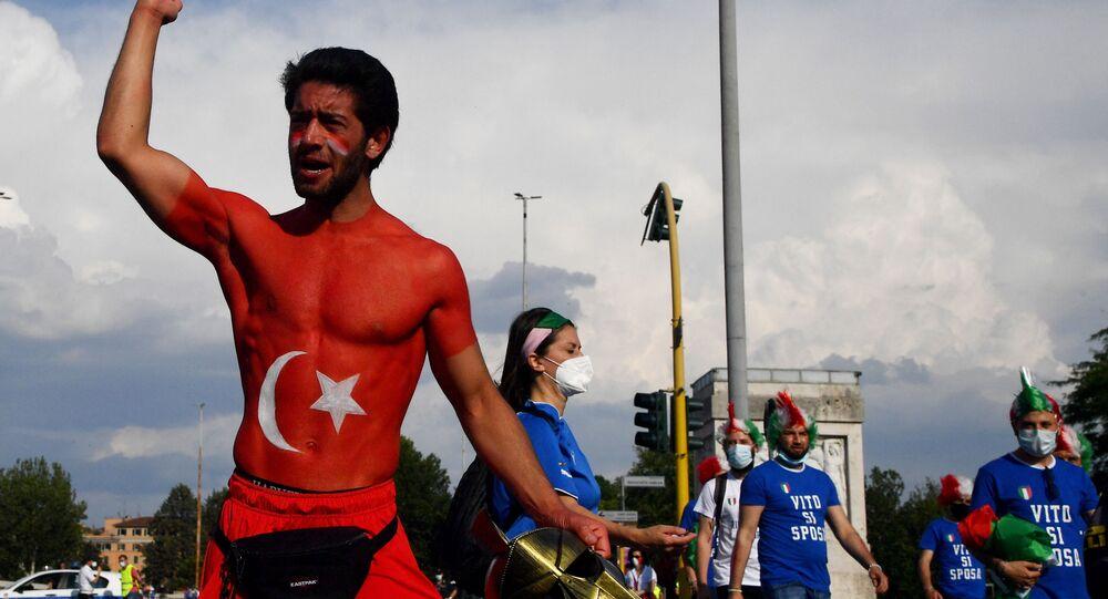 يهتف مشجع تركي (يسار) بينما يمر مشجعو منتخب إيطاليا بالقرب من الملعب أولمبكو، في روما، قبل انطلاق المباراة بين تركيا وإيطاليا،  في 11 يونيو 2021 .