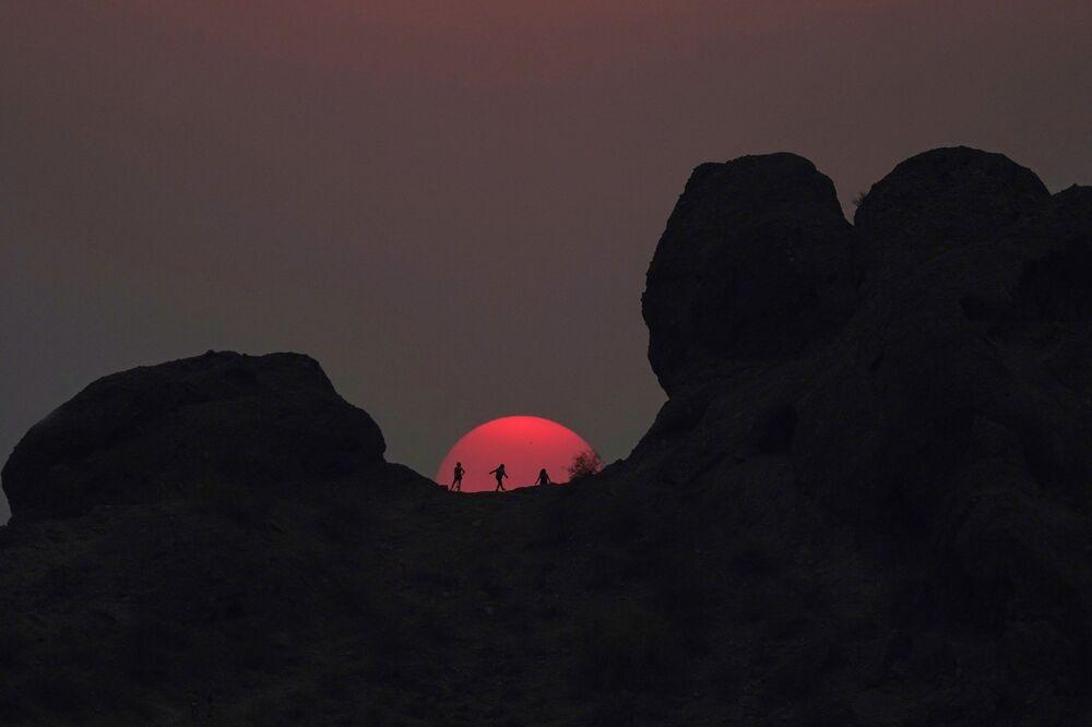متنزهون يتوقفون لمشاهدة غروب الشمس في حديقة باباغو خلال موجة حارة، حيث وصلت درجات الحرارة إلى 115 فهرنهايت (46.1 سلسيوس) في  فينيكس، الولايات المتحدة 15 يونيو 2021