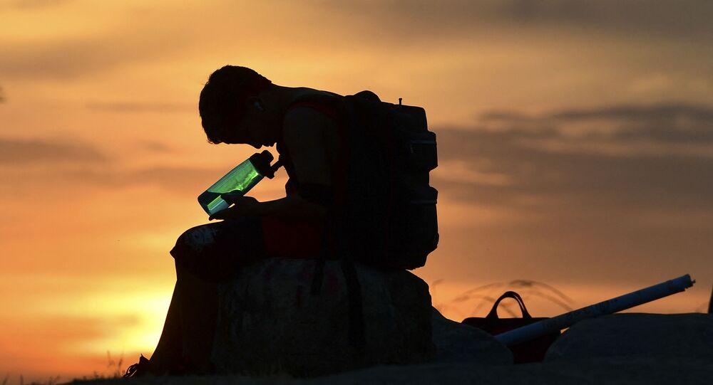 طفل ينظر إلى زجاجة المياه الخاصة به على خلفية غروب الشمس في لوس أنجلوس،  مع ارتفاع درجات الحرارة في موجة الحر في بداية موسم الحر في كاليفورنيا، الولايات المتحدة،  في 15 يونيو 2021