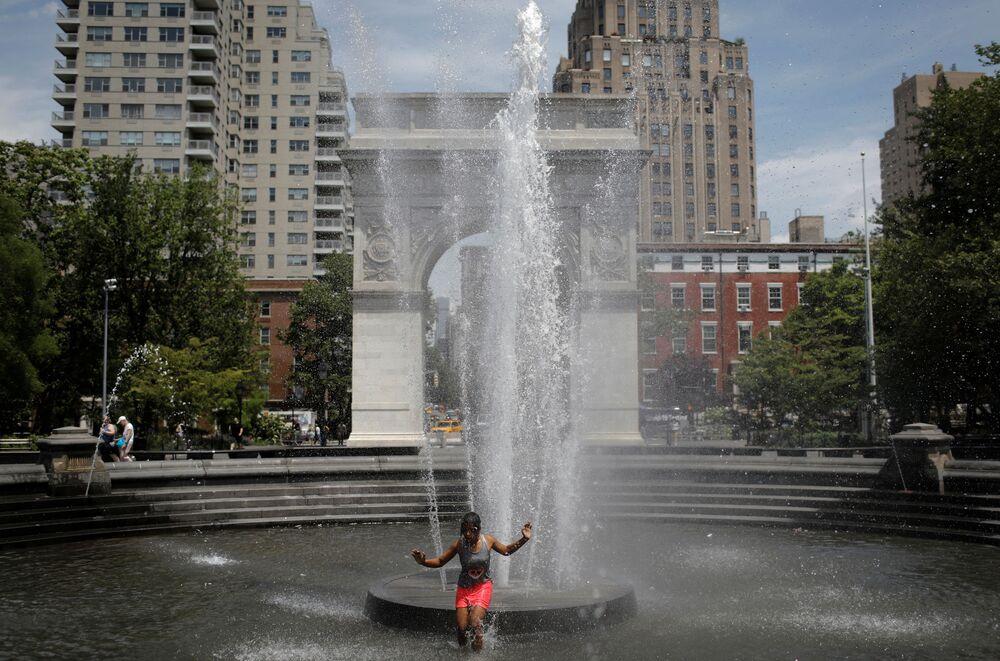 فتاة صغيرة تدخل في نافورة واشنطن سكوير في حديقة واشنطن سكوير، أثناء الطقس الحار في حي مانهاتن في مدينة نيويورك، ولاية نيويورك، الولايات المتحدة، 8 يونيو 2021