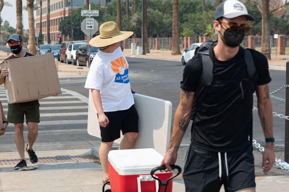 متطوعون ينقلون إمدادات المياه والثلج لتوزيعها على المشردين في فينيكس، ولاية أريزونا، في 15 يونيو 2021.