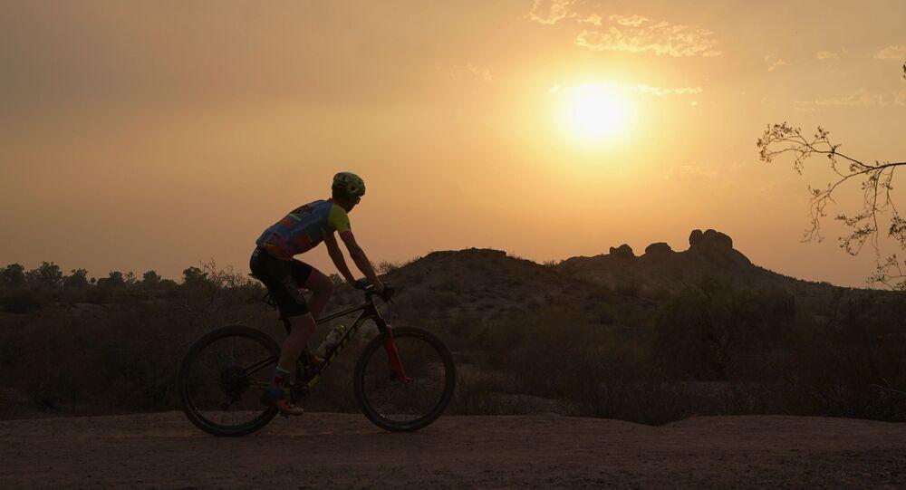 راكب دراجة بعد غروب الشمس في حديقة باباغو خلال موجة حارة في فينيكس، ولاية أريزونا، الولايات المتحدة، 15 يونيو 2021.