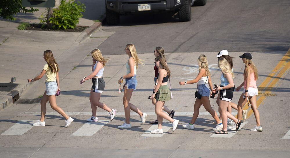 مع ارتفاع درجات الحرارة إلى أكثر من ثلاث درجات، يسير صف من الفتيات على طول شارع ماركت في وقت متأخر من يوم حار في دنفر، الولايات المتحدة 15 يونيو 2021