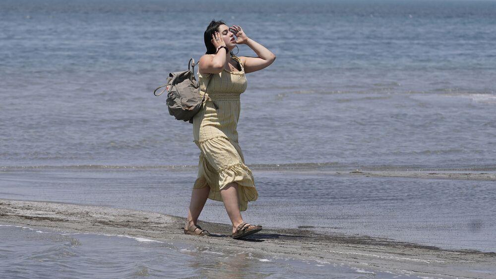 فتاة تسير على طول بحيرة سولت ليك الكبرى يوم 15 يونيو 2021، بالقرب من مدينة سولت ليك. حيث تم تسجيل رقماً قياسياً آخر في درجات الحرارة ، 15 يونيو 2021