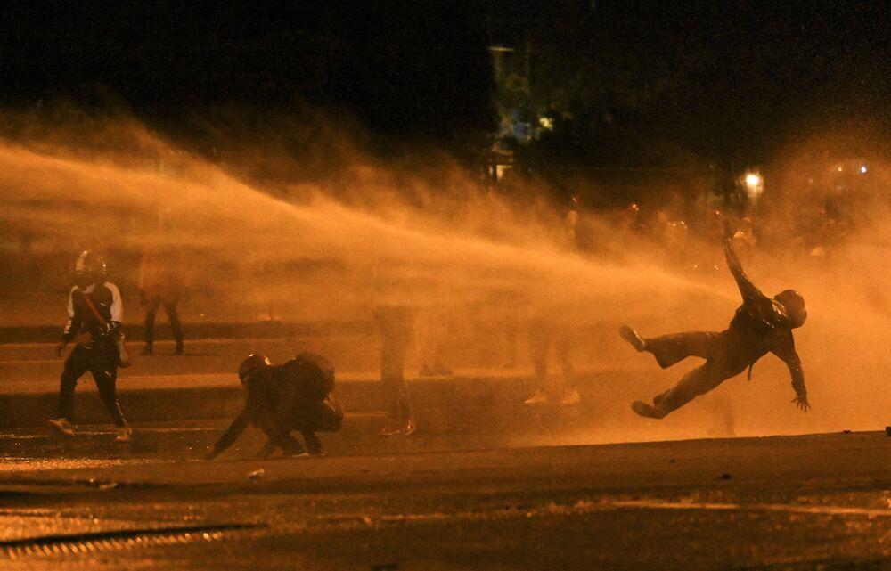 سقوط أحد المتظاهرين جراء إصابتهم بخراطيم المياه ، خلال اشتباكات مع شرطة مكافحة الشغب وسط احتجاجات مستمرة ضد حكومة الرئيس الكولومبي إيفان دوكي في بوغوتا، 12 يونيو 2021