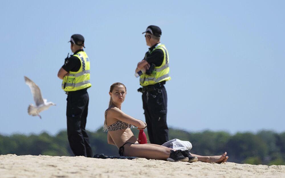 امرأة بريطانية تستجم على الشاطئ، أثناء قيام دورية للشرطة في مكان قريب، أثناء اجتماع لقادة مجموعة السبع في سانت آيفز، كورنوال، إنجلترا، 12 يونيو 2021.