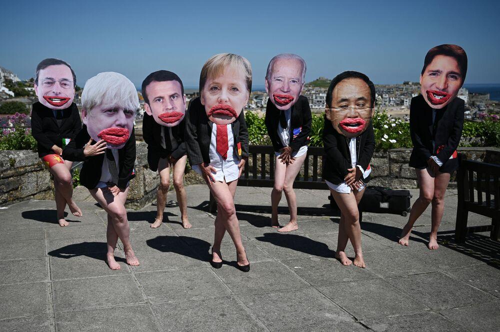 نشطاء بيئيون من حركة تمرد الانقراض يقفون مرتدين أقنعة لوجوه قادة مجموعة السبع في فعالية احتجاجية لتسليط الضوء على عدم المساواة بين الجنسين في السياسة في سانت إيفز، كورنوال خلال قمة مجموعة السبع في 13 يونيو 2021.
