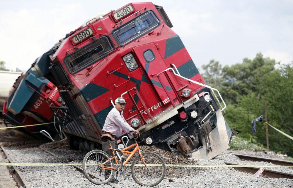 رجل يمر بدراجته عبر السكة الحديدية، على خلفية قطار خرج عن مساره في مجتمع سان إيسيدرو مازاتيبيك في تالا، ولاية خاليسكو، المكسيك،  15 يونيو 2021