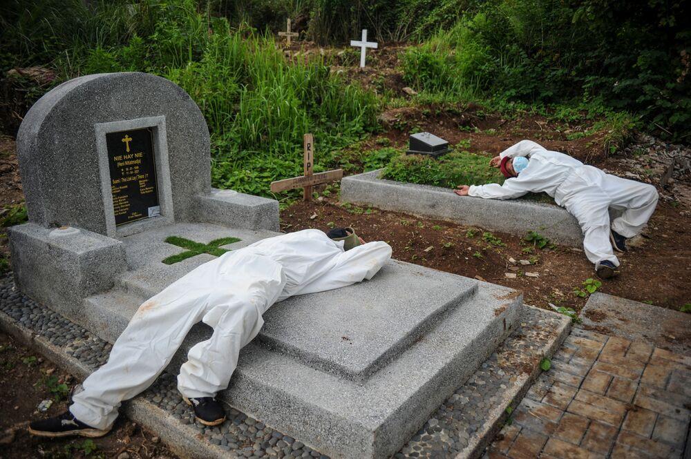 عمال يرتدون بدلات واقية، يستريحون بعد دفن ضحايا مرض كوفيد-19 في باندونغ، مقاطعة جاوة الغربية، إندونيسيا، في هذه الصورة التي التقطتها أنتارا فوتو  15 يونيو 2021