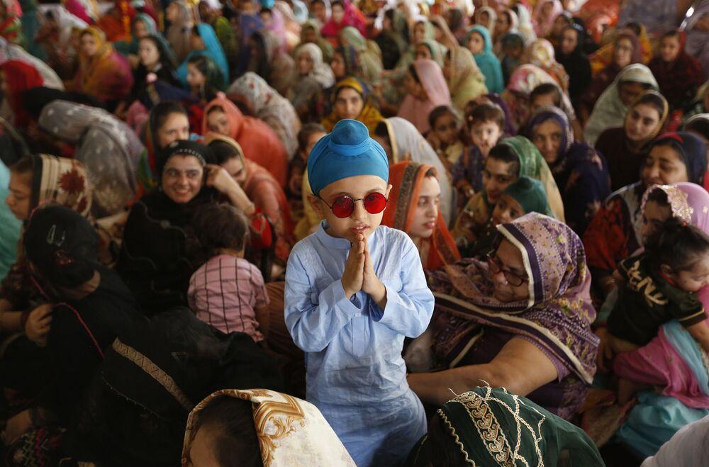 طفل من الديانة السيخية، يقف بجانب والدته في حفل لإحياء الذكرى الـ 415 لاستشهاد غورو أرجان ديف جي، في غورودوارا ديرا صاحب، في لاهو ، باكستان، 16 يونيو 2021