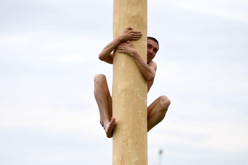 أحد المشاركين يتسلق العامود في  فعالية الاحتفال بالعيد الوطني السنوي سابانتوي في نيجنكامسك الروسية، 12 يونيو 2021