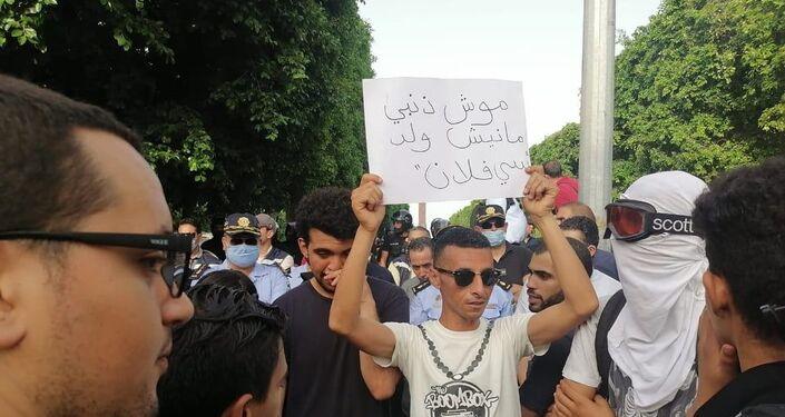 شاب يرفع لافتة خلال مسيرة في شارع الحبيب بورقيبة بتونس للتنديد بقمع الشرطة للاحتجاجات الأخيرة