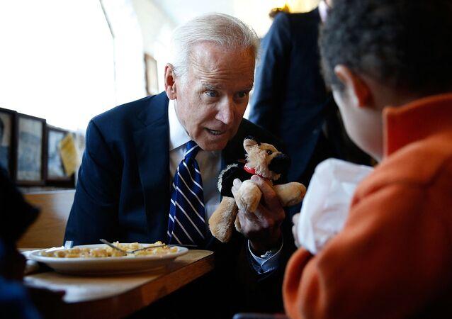 الرئيس الأمريكي جو بايدن يمنح طفلا لعبة محشوة على شكل كلبه تشامب
