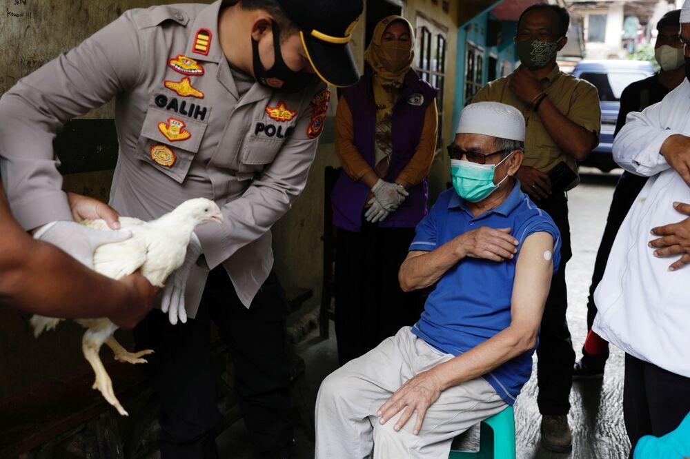 رئيس شرطة المنطقة، غاليه أبريا، يمنح دجاجة حية لجيجي جاينودين، البالغ من العمر 68 عامًا، من قرية سينداغلايا، الذي تلقى للتو جرعته الأولى من لقاح كوفيد-19، مقاطعة جاوة الغربية، إندونيسيا، 15 يونيو 2021.