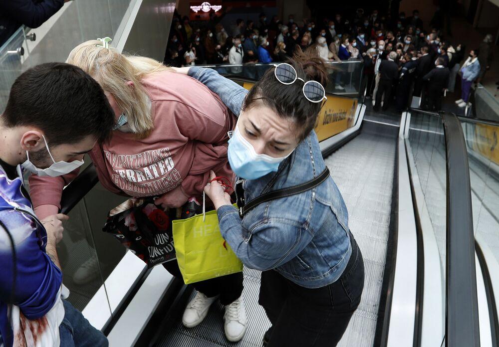 يتم مساعدة امرأة على صعود السلم المتحرك بينما يصطف الناس في طابور ليكونوا ضمن أول  100 شخص حصلوا على التطعيم، ويكون من نصيبهم بطاقات تسوق مجانية، في مركز التسوق Usce في بلغراد، صربيا، 6 مايو 2021