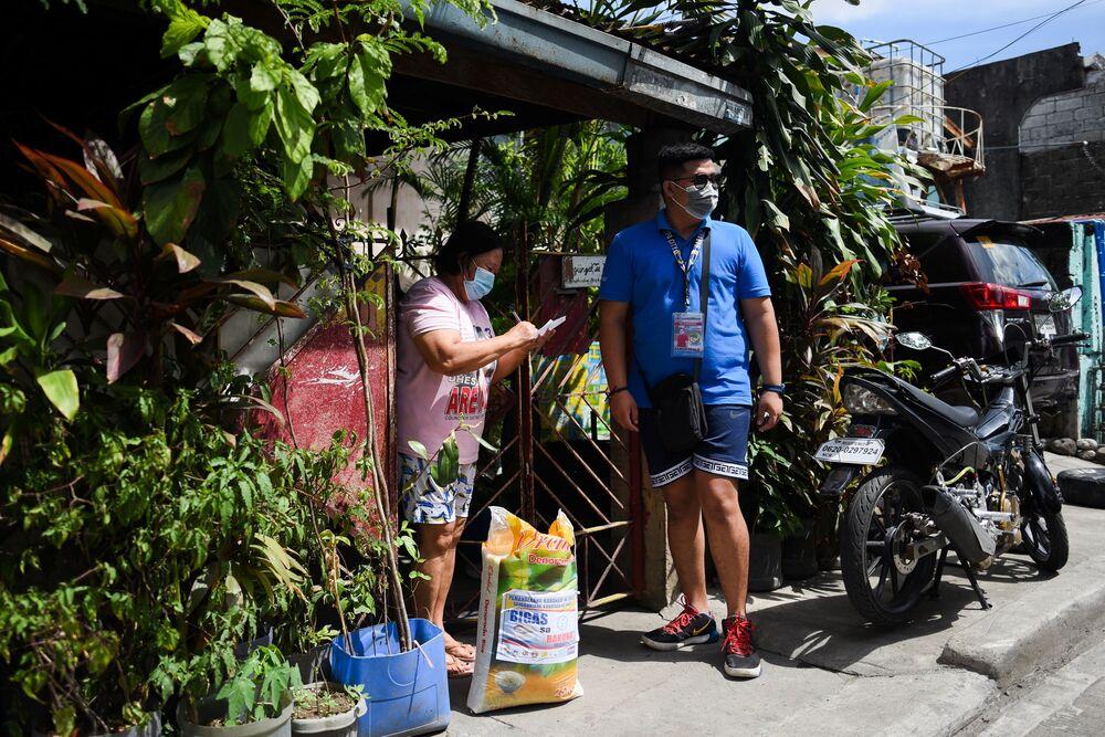 شاريتو نوفوينتي، موظفة في القطاع الصحي على مستوى القرية، تتلقى كيسا من الأرز الخاص بها بعد فوزها في السحب الأسبوعي للمقيمين الذين تم تطعيمهم ضد كوفيد-19، خارج منزلها ، في مدينة مونتينلوبا، مترو مانيلا، الفلبين، 20 يونيو 2021