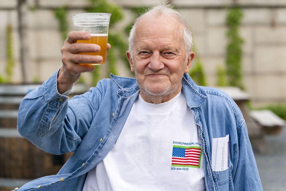 في هذه الصورة بتاريخ 6 مايو 2021، جورج ريبلي، 72 عامًا، من واشنطن، يحمل بيرة مجانية بعد تلقيه لقاح جي أند جي ضد مرض كوفيد- 19، في ذا ريتش في مركز كينيدي في واشنطن. البيرة المجانية هي أحدث حافز يدعمه البيت الأبيض للأمريكيين لتطعيمهم ضد كوفيد- 19.