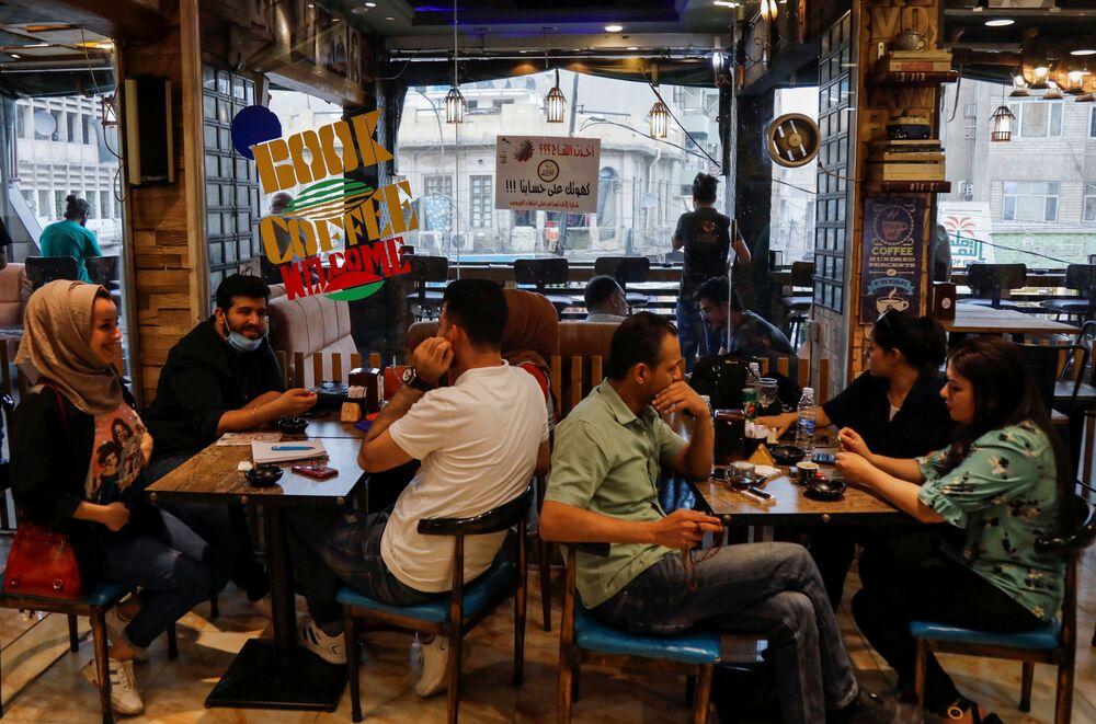 الزبائن يجلسون في مقهى، حيث تُقدم قهوة مجانية للأشخاص الذين تلقوا لقاحاً ضد مرض كوفيد-19 في بغداد، العراق ، 22 مايو 2021