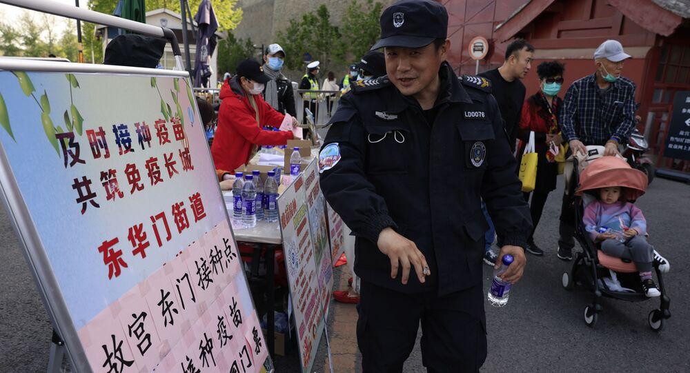 حارس أمن يتلقى ملصقًا يعلن أنه تم تطعيمه ضد فيروس كورونا خارج مدخل المدينة المحرمة في بكين، الصين 14 أبريل 2021
