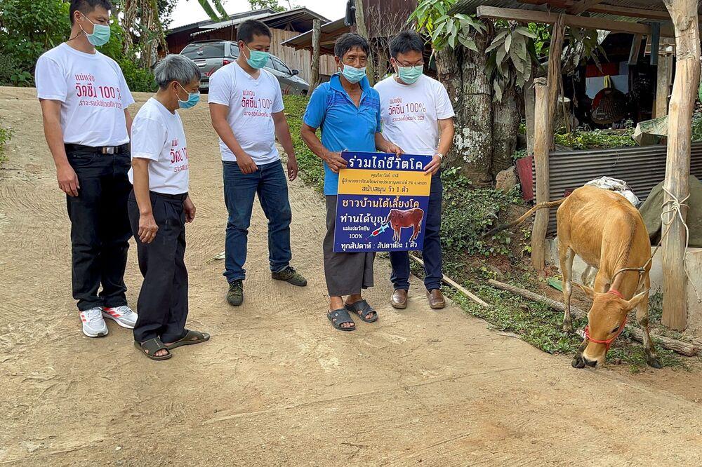 رجل يحمل لافتة بعد فوزه في حملة يانصيب للمقيمين الملقحين للفوز ببقرة حية أسبوعيًا، في إطار تعزيز حملة التطعيم المحلية ضد كوفيد-19 في مقاطعة شيانغ ماي، تايلاند، 8 يونيو 2021