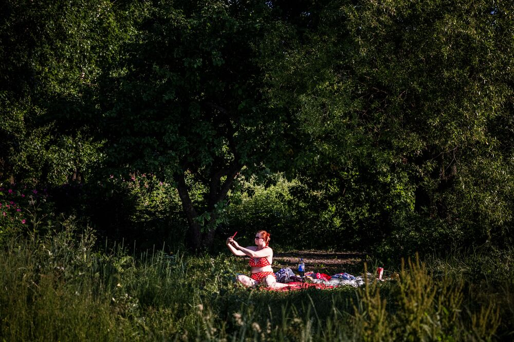 امرأة تلتقط صورة سيلفي خلال حمام شمسي