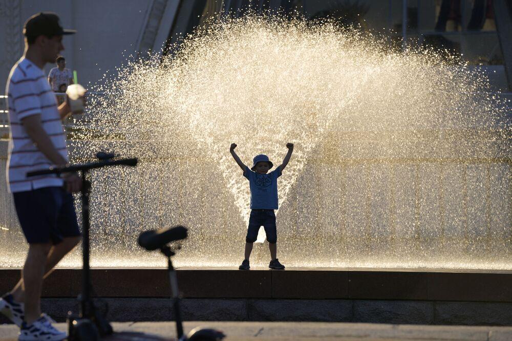 صبي يقف بالقرب من نافورة مياه