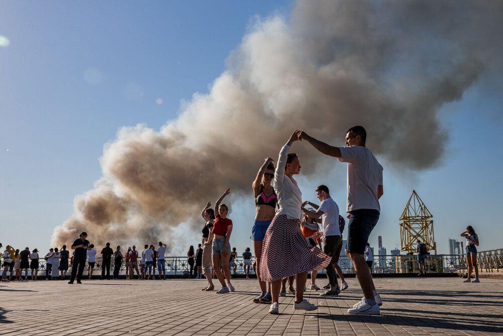 أزواج يرقصون السامبا بينما يتصاعد الدخان من مستودع للألعاب النارية مشتعل في موسكو، روسيا 19 يونيو 2021