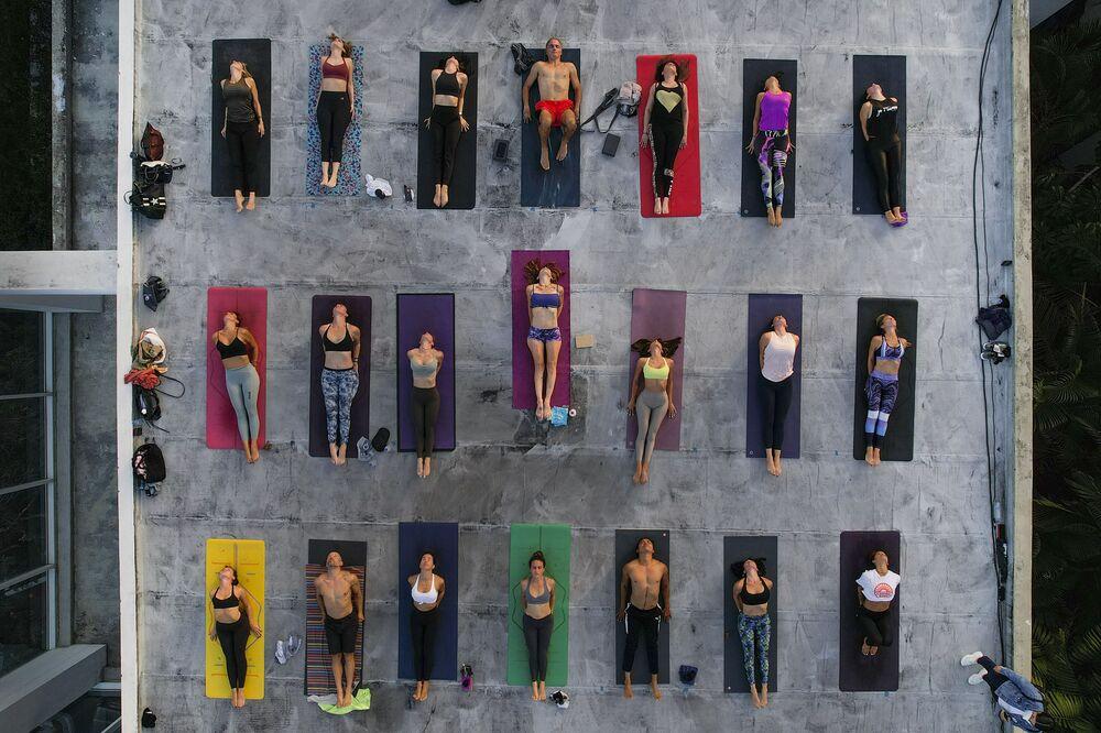 عشاق اليوغا في اليوم العالمي لليوغ، مع الحفاظ على قاعدة التباعد الاجتماعي كإجراء احترازي وسط جائحة كوفيد-19، على سطح استوديو - في كاراكاس، فنزويلا ، 21 يونيو 2021