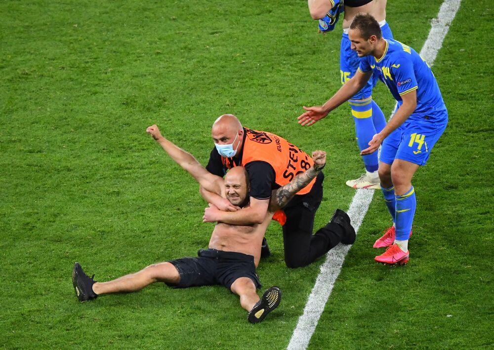 مباراة دور الـ 16 من بطولة يورو 2020 - عناصر الأمن تقوم بإبعاد مشجع من أرض ملعب هامبدن بارك خلال مباراة إنجلترا وأوكرانيا في غلاسكو، اسكتلندا، بريطانيا 29 يونيو 2021