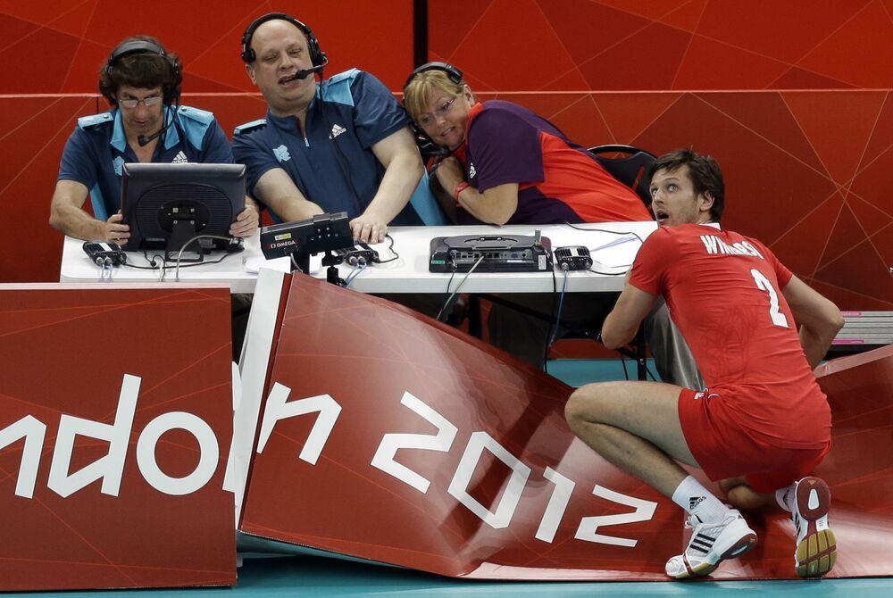 ينظر البولندي ميشال وينارسكي (صاحب رقم 2) إلى الوراء بعد اصطدامه بالجدار الخلفي للجنة التحكيم، ليحتفظ بتسديدة ضد بلغاريا خلال مباراة أولية للكرة الطائرة للرجال، في دورة الألعاب الأولمبية الصيفية 2012، 31 يوليو  2012، في لندن