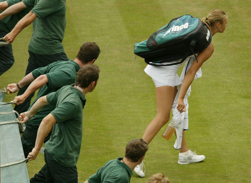 أفراد طاقم العمل في الملعب ينتظرون خروج لاعبة التنس الروسية ماريا شارابوفا من الملعب، لتغطيته من المطر، خلال توقف مباراة فردية السيدات، في نصف النهائي ضد ليندساي دافنبورت في الملعب الرئيسي في ويمبلدون،1 يوليو 2004