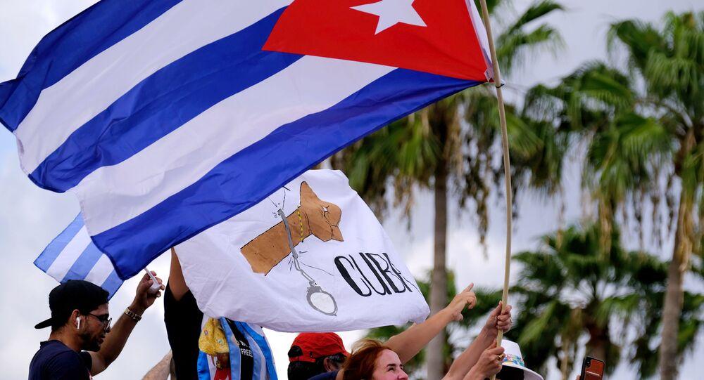 المهاجرون في ليتل هافانا يلوحون بالأعلام الكوبية أثناء ردهم على تقارير الاحتجاجات في كوبا ضد الاقتصاد المتدهور