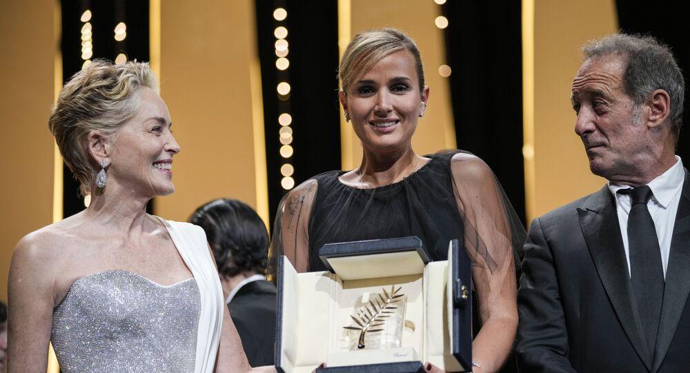 المخرجة جوليا دوكورنو، في الوسط، تحمل السعفة الذهبية لفيلم تيتان