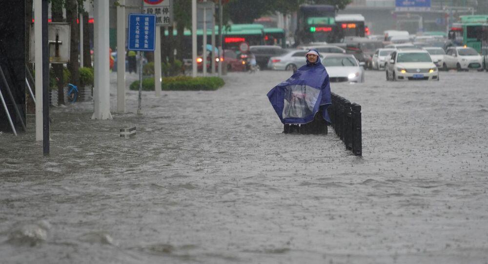 ساكن يرتدي غطاء مطر يقف على طريق غمرته المياه في مدينة تشنغتشو بمقاطعة خنان الصينية 20 يوليو 2021