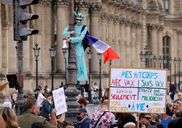 متظاهر يرتدي زي تمثال الحرية يشارك في احتجاجات ضد الإجراءات الجديدة التي أعلنها الرئيس الفرنسي إيمانويل ماكرون لمكافحة تفشي فيروس كورونا (كوفيد -19) في باريس، فرنسا، 17 يوليو 2021.