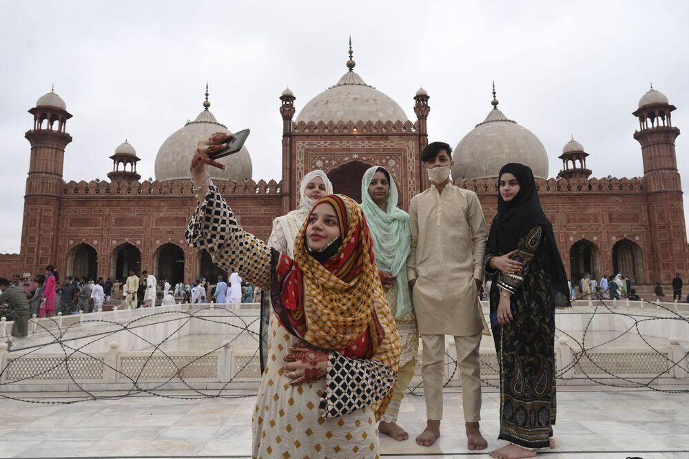 امرأة تلتقط صورة سيلفي مع صديقاتها بعد أداء صلاة عيد الأضحى في مسجد بادشاهي التاريخي في لاهور، باكستان21 يوليو 2021