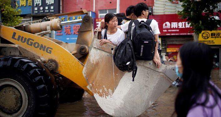 أشخاص يركبون جرافة في طريق غمرته مياه الفيضانات في مدينة تشنغتشو بمقاطعة هينان، الصين 22 يوليو 2021