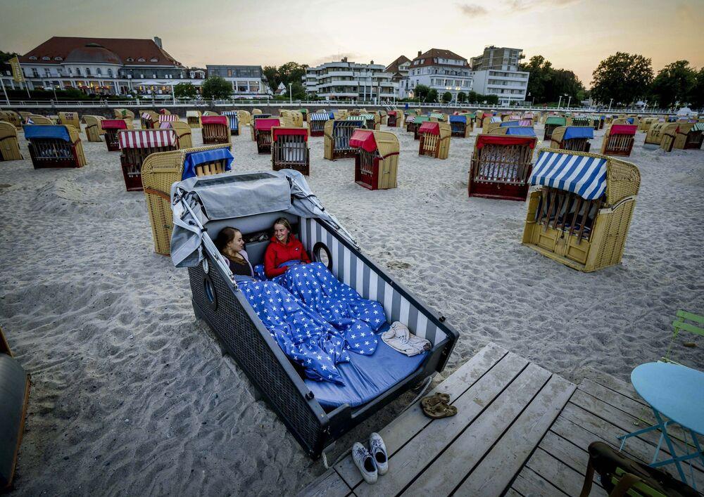 شابتان تستعدان لقضاء الليل داخل مقعد الشاطئ المصمم خصيصًا على شاطئ بحر البلطيق في ترافيمويندي، ألمانيا 18 يوليو 2021