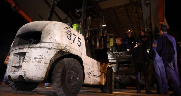 العمال يحاولون تفريغ شحنات المساعدات الطبية المقدمة من روسيا إلى سوريا